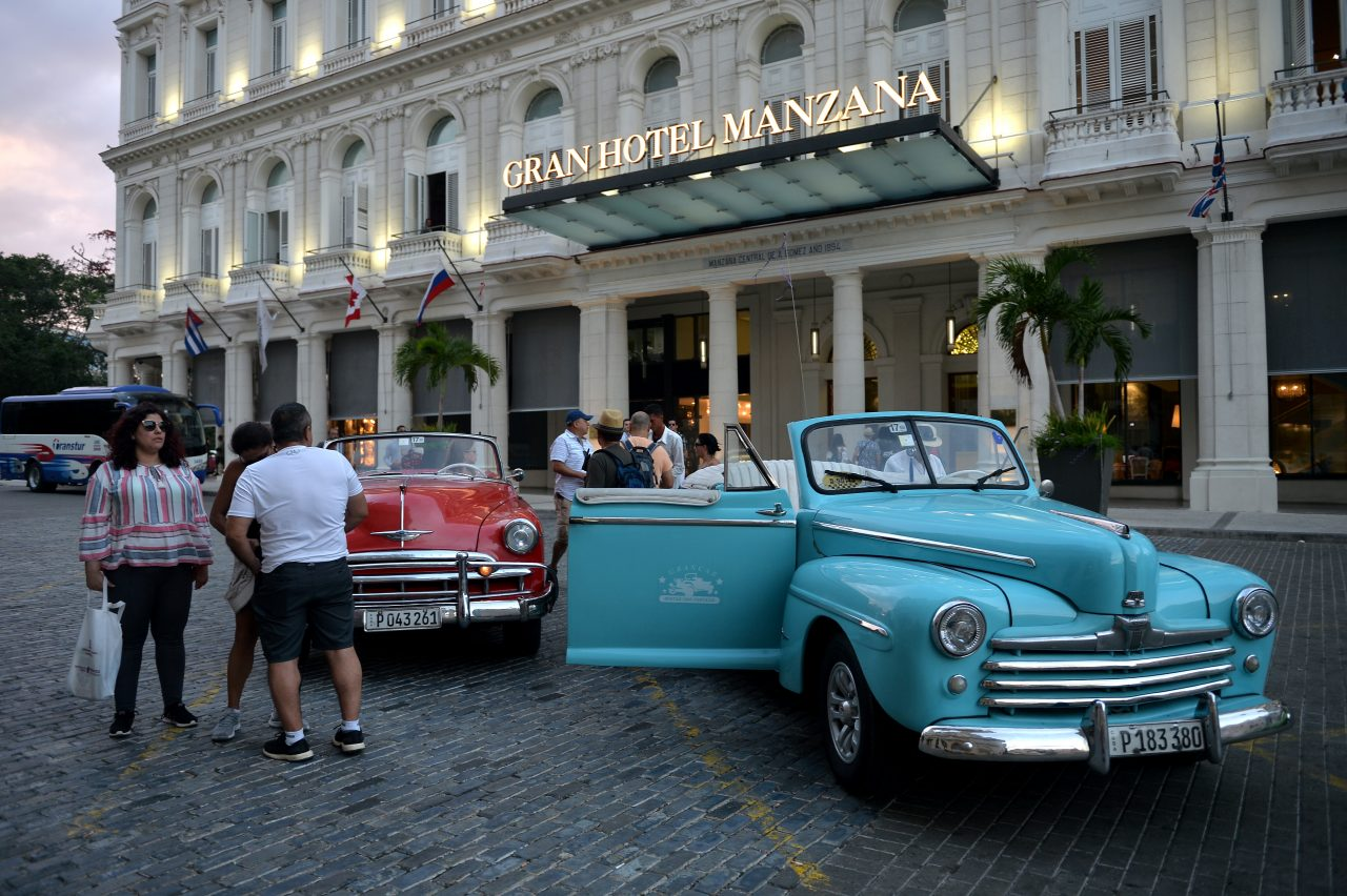 Tourists stand next to an old American car in front of the Gran Manzana Hotel in Havana, on February 11, 2019. - Cuba attracts wealthy tourists with five-stars hotels, spas and luxury brands.