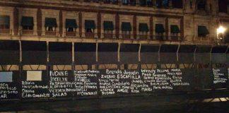 Mujeres escriben nombres de víctimas de feminicidio en muro que resguarda Palacio Nacional